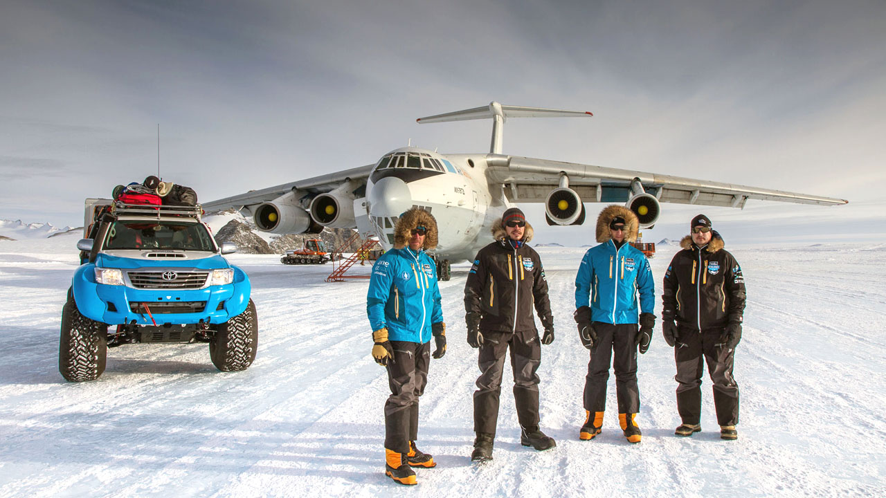 Четыре гонщика на фоне самолета