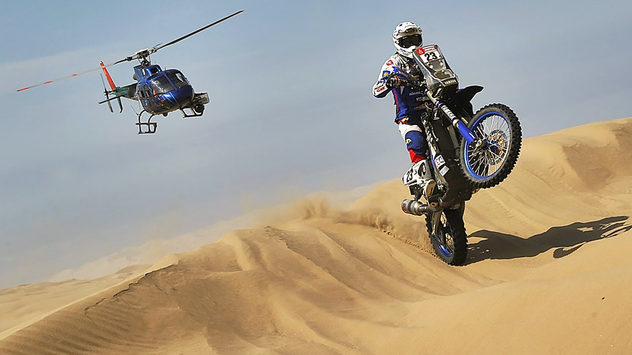 Вертолет снимает мотоциклиста в пустыне